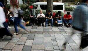 People sit in queue for the release of Apple's new iPhone 7 and 7 Plus in front of the Apple Store in Tokyo's Omotesando shopping district